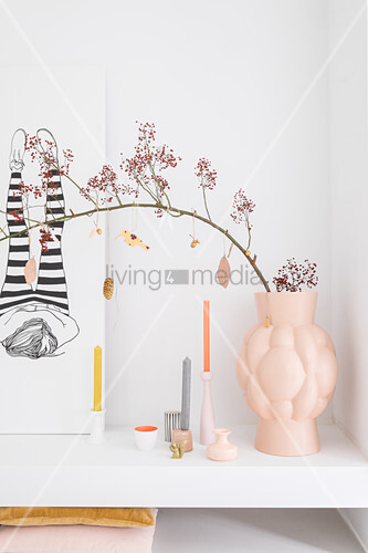 Branch of berries in large vase on white masonry shelf