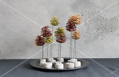 Painted pine cones on wire stands with concrete bases