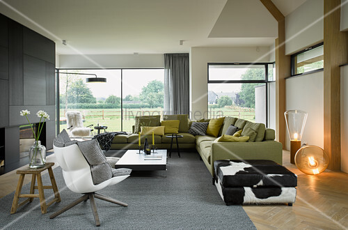 Modern living room with glass wall overlooking large garden