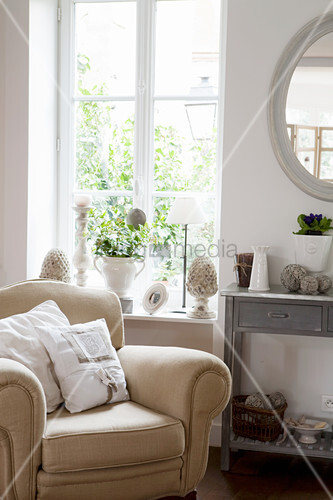 Cream armchair next to window with French-style accessories on windowsill