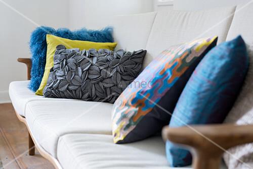 Bunte Kissen mit verschiedenen Texturen auf dem Sofa