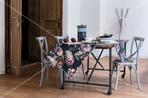 Geblümter Stoff auf einem rustikalen Tisch mit grauen Bistrostühlen