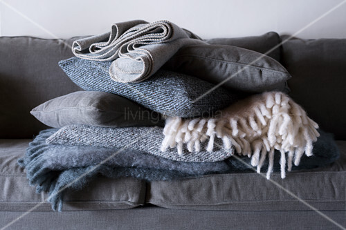 Stack of folded woollen blankets and cushions on grey sofa