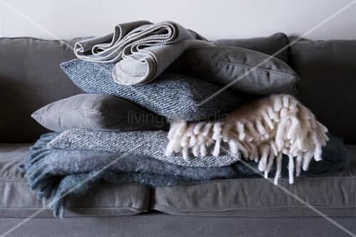 Stapel gefalteter Wolldecken und Kissen auf dem grauen Sofa
