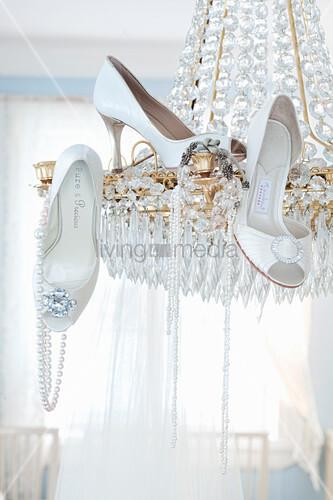 Elegante, weiße Pumps und Perlenketten hängen am Kronleuchter