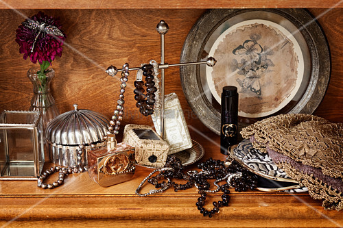 Vintage lady's accessories: jewellery box, perfume bottle, bracelets and necklaces in wooden cabinet