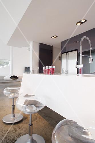 Transparente Barhocker an der weißen Küchentheke