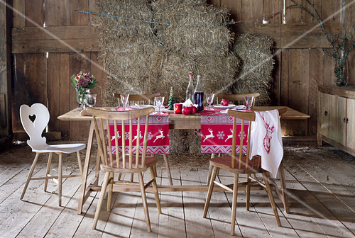 Table set for Christmas with red and white runners in rustic barn