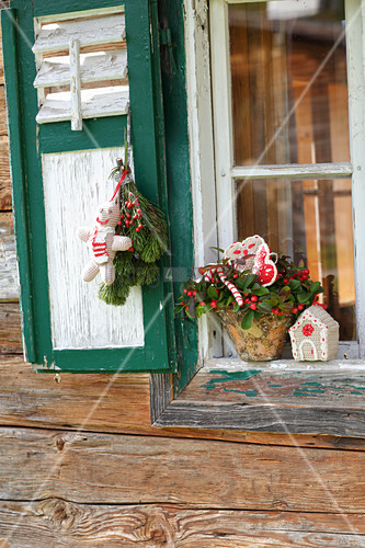 Christmas arrangement of snowberries and conifer posies on outside windowsill