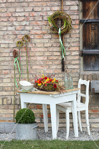 Arrangement of red and yellow tulips, narcissus and ranunculus on table and wreath of twigs on walls