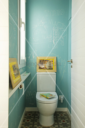 Children's drawings on blue walls in toilet