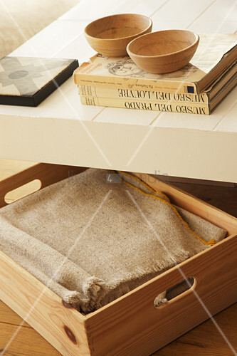 Decke in einer Holzkiste unter dem Couchtisch mit Büchern und Schalen