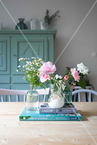 Fresh garden flowers in three small vases and books on table