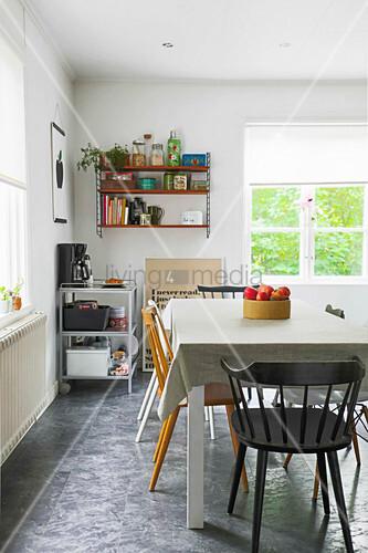 Verschiedene Sprossenstühle um den Esstisch in der Wohnküche