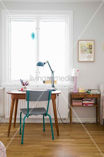 Kinderstuhl am alten Schreibtisch unter dem Fenster