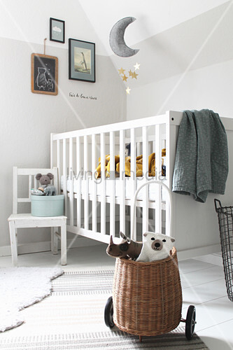 Soft toys in basket on wheels, white child's chair and cot