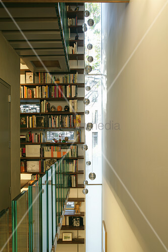 Narrow, vertical strip window and bookcase extending over three storeys