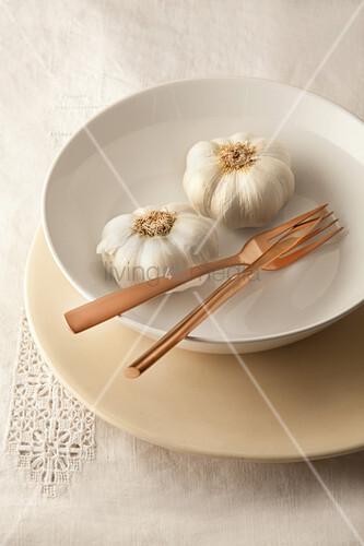 Fresh garlic and cutlery in bowl