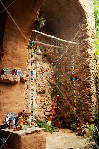 Rustikale Aussendusche mit Fadenvorhang in Naturstein-Nische