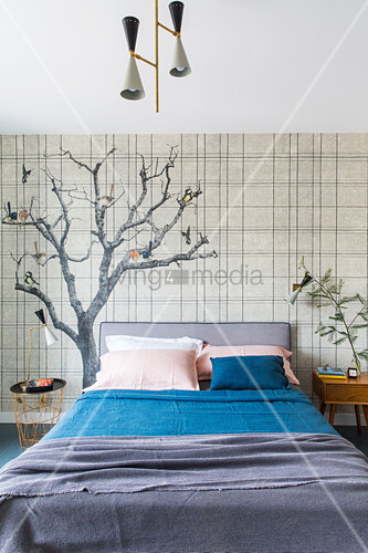 Double bed against wallpaper with tree motiv