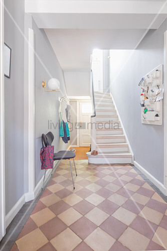 Chequered floor and staircase in bright hallway