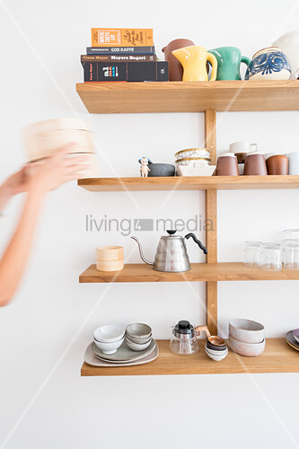 Hands removing item from shelves of crockery and kitchen utensils