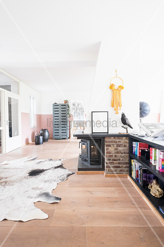 Open-plan living space with log-burner and cowhide rug on gallery