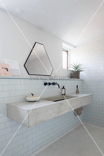 Concrete washstand in purist bathroom with small window