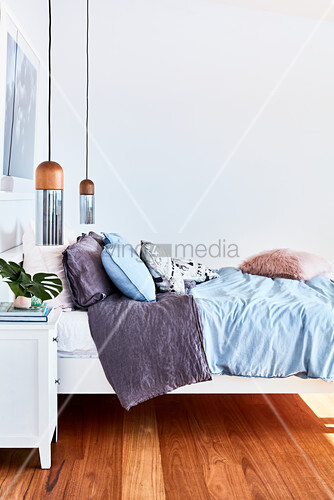 Bed with pendant lamps and bedside cabinet in bedroom