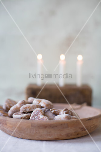 Gingerbread hearts in wooden bowl in front of three lit candles