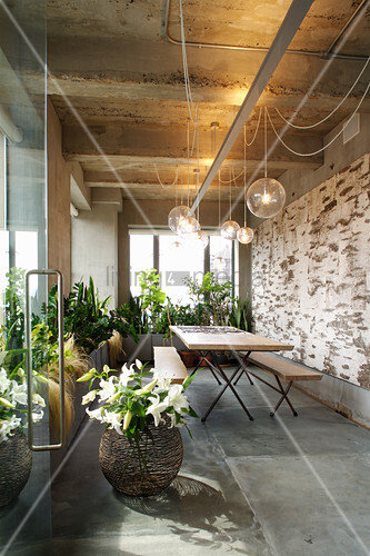 Table and benches below pendant lamps and large houseplants in loggia