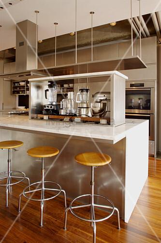 Kücheninsel mit verschiedenen Küchengeräten und Barhockern in eleganter, offener Küche