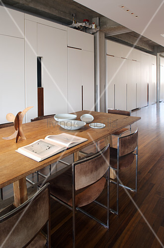 Long wooden table and chairs with suede covers in front of fitted cupboards in loft apartment