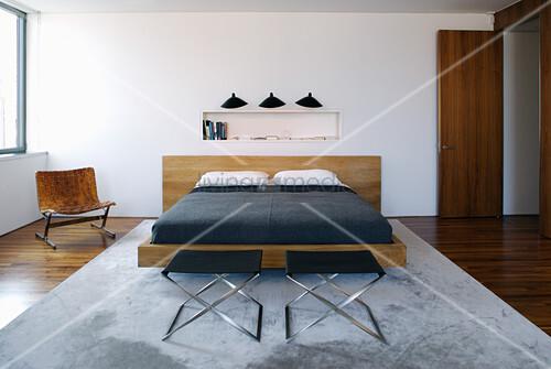Elegantes Doppelbett und Designerstuhl im Schlafzimmer
