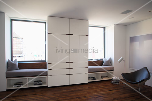 White, floor-to-ceiling wardrobe flanked by window seats fitted in window niches