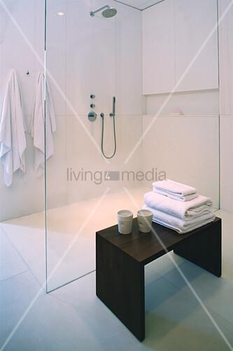 Hocker mit Handtüchern und Bechern vor verglastem Duschbereich
