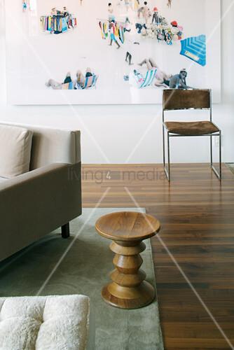 Designer-Beistelltisch aus Holz neben Sofa, im Hintergrund Stuhl vor moderner Fotomontage