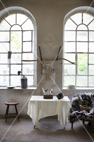 Bowls and collection of feathers on table, furry blanket on chair and stool below arched windows in loft apartment