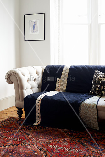 Dark blue quilt on pale button-tufted sofa