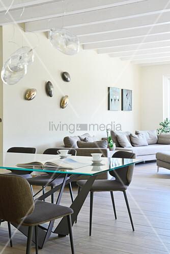 Glastisch mit gepolsterten Stühlen und Designerleuchte, im Hintergrund Sofagarnitur in offenem Wohnraum