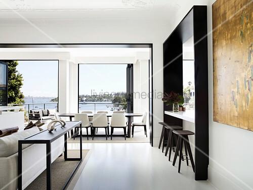 Theke mit Barhockern, Essbereich vor Fenster mit Meerblick und Lounge in Designerstil