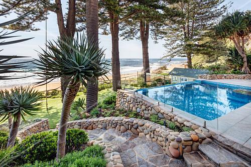 Pool umgeben von Palmen und Bäumen im Garten mit Meerzugang