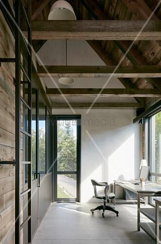 Schreibtisch an der Fensterfront unter dem offenen Dach mit Balken