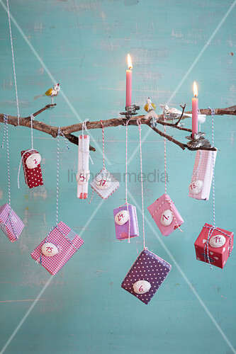 Advent calendar handmade from branch, candles, bird ornaments and small packages