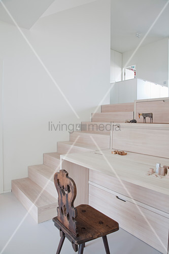 Fitted desk and storage modules next to steps leading to raised level