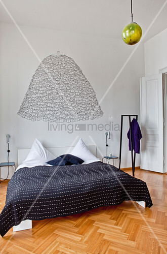 Black bedspread on double bed, free-standing clothes rack and wall decal
