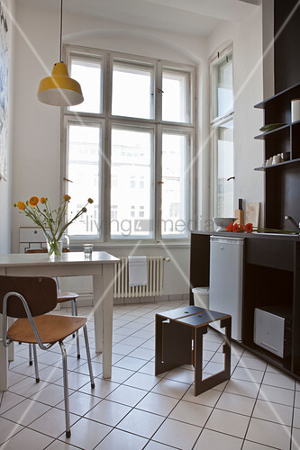 Table and two chairs in black-and-white kitchen of period apartment