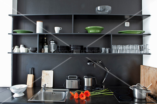 Shelves on black wall above black kitchen counter