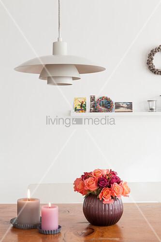 Vase mit Rosen und zwei Kerzen auf Holztisch, darüber Klassiker-Hängelampe