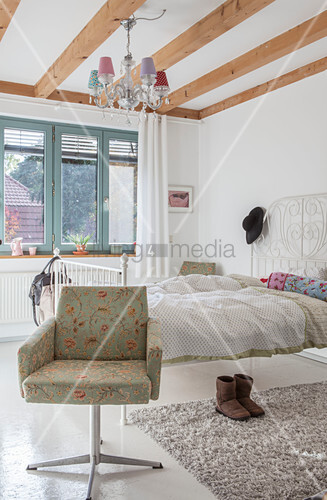 Armchair and white metal bed in bright bedroom